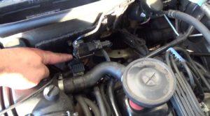 Mão apontando válvula solenoide no motor do carro