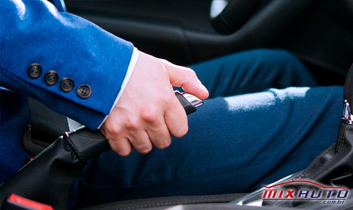 Homem branco de terno azul sentado no banco do motorista manipulando o freio de mão do carro