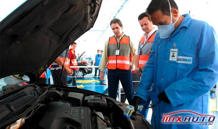 Gilberto Kassab junto a mecânico de uniforme azul durante Inspeção Veicular