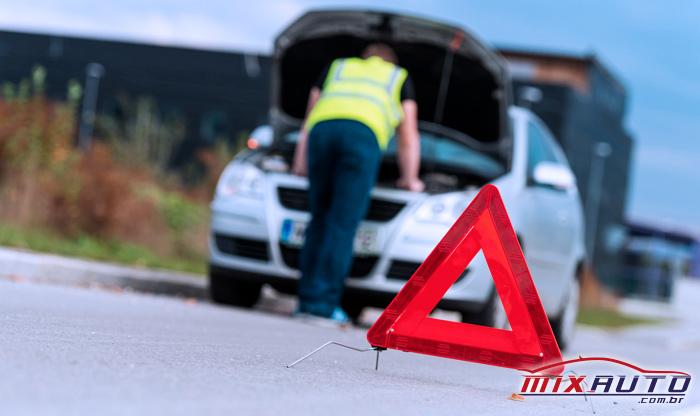 Triângulo para sinalização em foco e à frente de homem com colete de trânsito parado em frente a carro prateado com o capô levantado