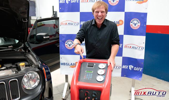 Apresentador Ciro Bottini apontando para o aparelho que realiza a carga de gás do ar condicionado automotivo