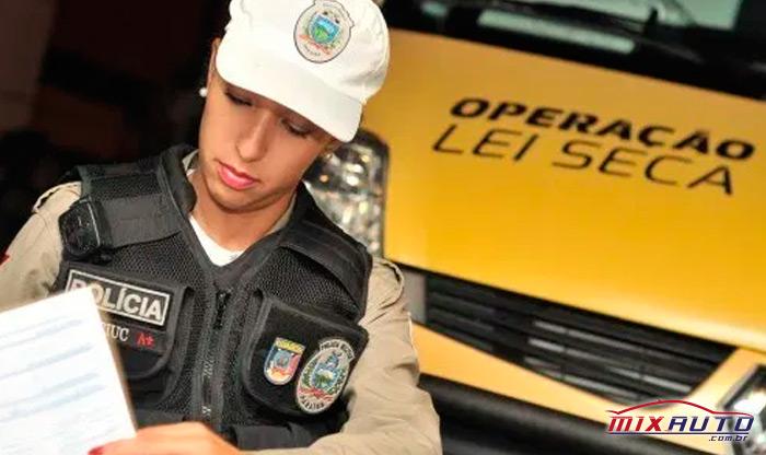 Policial realizando vistoria em frente à carro da Lei Seca durante blitz de segurança