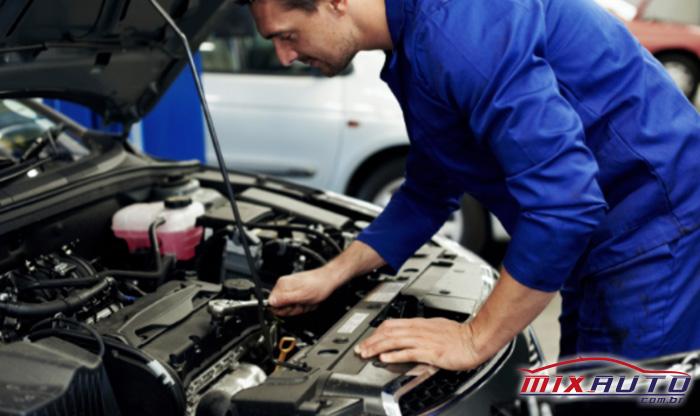 Imagem de um mecânico realizando a manutenção preventiva automotiva do motor