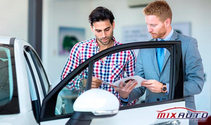 Foto de duas pessoas olhando o manual para verificar quando a manutenção preventiva automotiva deve ser realizada