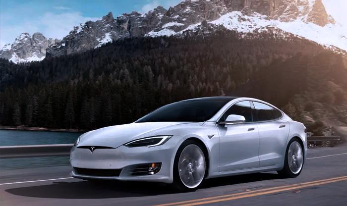 Tesla S Model sedã em movimento por estrada com alpes e rio cristalino ao fundo