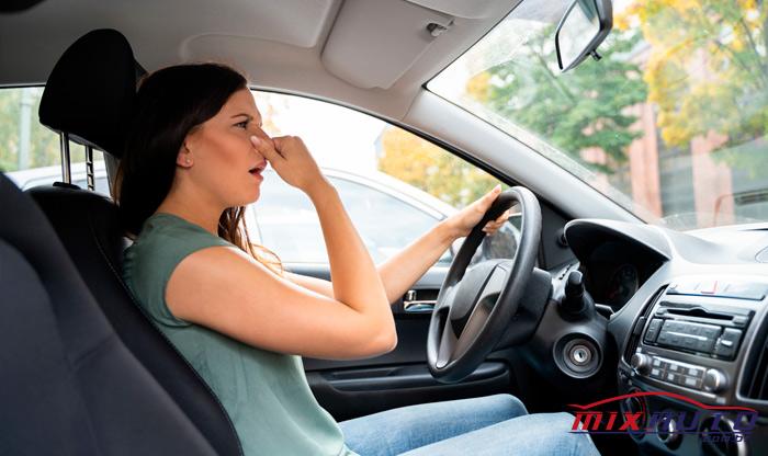 Mulher tapando o nariz dentro do carro por conta do mau-cheiro do ar-condicionado automotivo