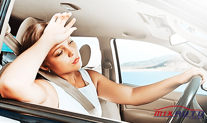 Mulher sofrendo calor dentro do carro remete à necessidade do ar-condicionado automotivo