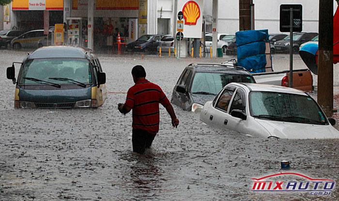 Homem anda na rua alagada entre os carros que estão sendo atingidos pela água
