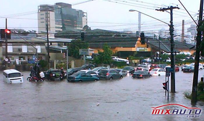 Trânsito formado em avenida enquanto os carros estão sendo submersos pela água da enchente