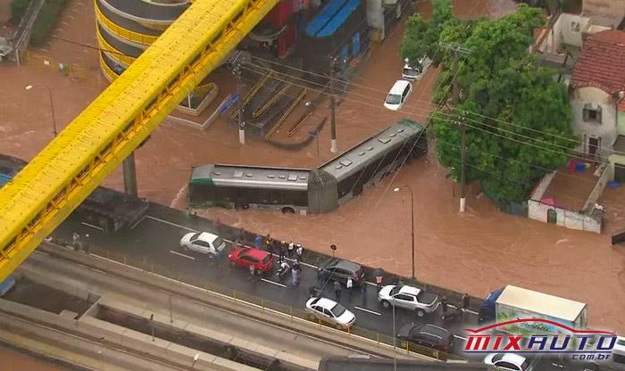 Carros e caminhões em uma ponte e um ônibus passando por uma rua alagada
