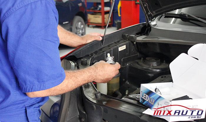 Mecânico segurando uma lâmpada automotiva para fazer a troca