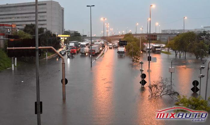 Carros, motos e caminhões esperando a água da enchente baixar para continuar o trajeto