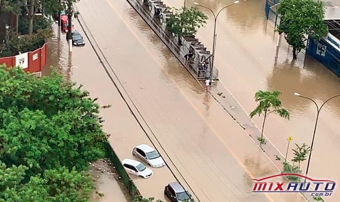 Carros sendo atingidos pela água da enchente em avenida de São Paulo