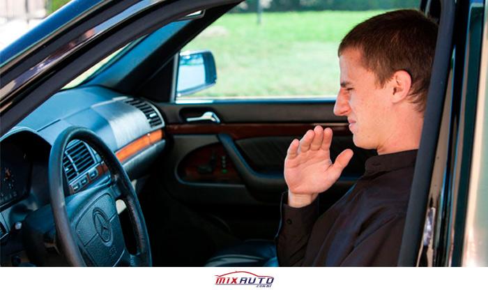 Jovem sentado no banco do motorista de um Mercedes gesticula e faz careta indicando mau cheiro