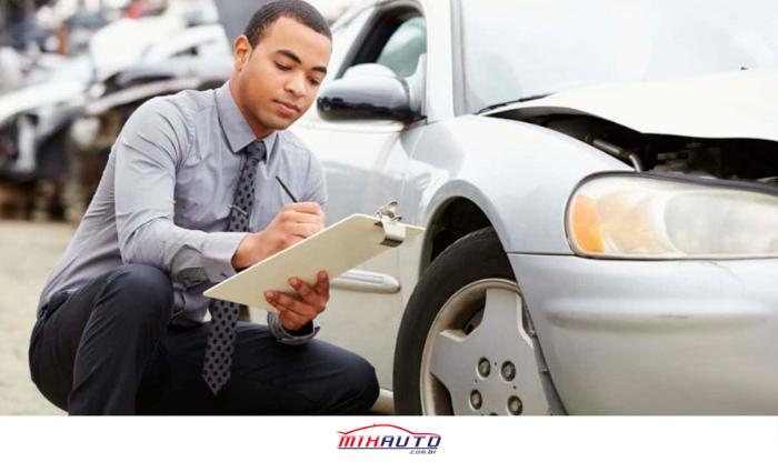 Homem abaixado ao lado de um carro com uma prancheta, anotando resultados da vistoria veicular